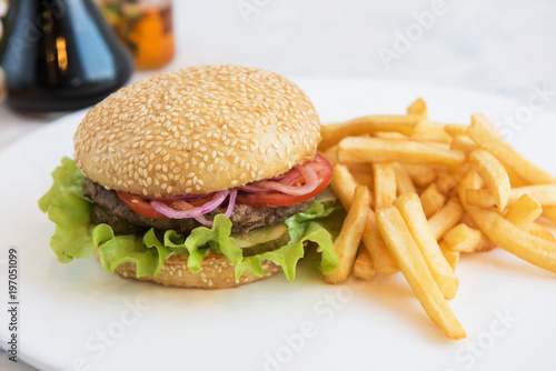 Tasty classical burger with fried potato on white table - 197051099
