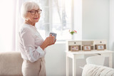 Caffeine lover. Pleasant pretty elderly woman standing half-turned in the living room and posing for the camera while holding a cup of coffee - 197054067