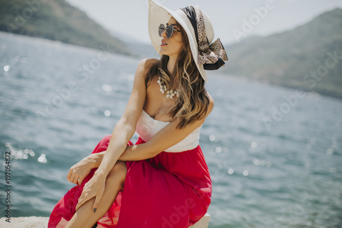 Pretty young woman sitting by the sea