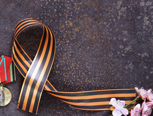 Poster symbol Victory Day ribbon and medals on an iron background