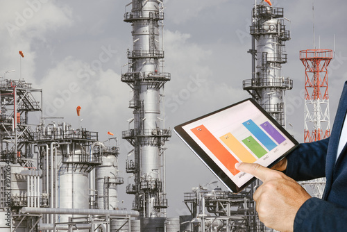 Staande foto Industrial geb. businessman fingers touching chart tablet against oil refinery in petrochemical Aerial view oil refinery night during twilight,Industrial zone,Energy power station