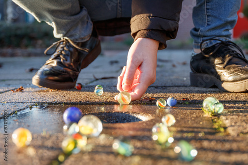 Dziecko bawić się z marmurami na chodniku. Staromodne zabawki są nadal w użyciu.