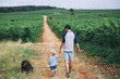 Father and son walking with dog on nature, outdoors.