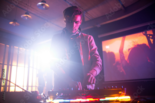 Portrait shot of handsome young DJ mixing music on console while entertaining guests at night club, lens flare