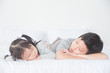 Two Asian siblings fall asleep on bed in day time