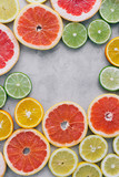 Top view frame offrom sliced citrus fruit on light background. Flat lay. Summer background