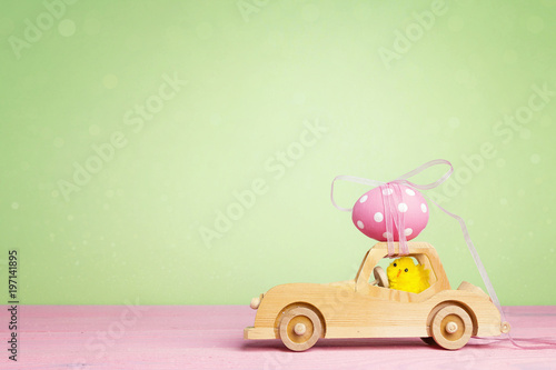 Wooden toy car with Easter egg on the roof and chick driver on green background.