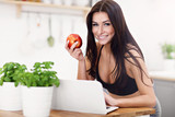 Fit smiling young woman with apple in modern kitchen - 197165275