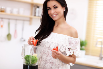 Fit smiling young woman preparing healthy smoothie in modern kitchen