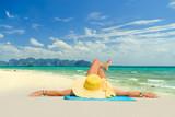 Woman in bikini wearing a yellow hat at tropical beach - 197169264