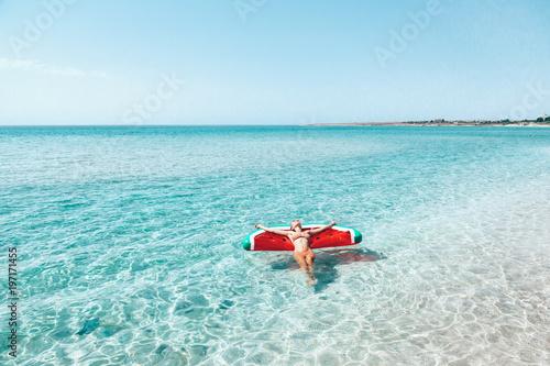 Woman on lilo on the beach
