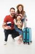 Portrait of happy family of tourists with suitcase isolated on white
