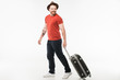 Stylish man in hat carrying suitcase isolated on white, travel concept