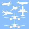 Vector Set of White Silhouette Passenger Planes on Blue Background.