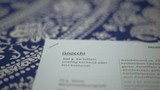 Recipe papers a top a blue flower patterned tablecloth. Rack focus. Selective focus. Overhead shot. Close up. Slow motion. - 197179878