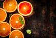 Fresh raw blood oranges, halves, with mint, on dark rusty background copy space top view