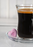 Espresso. Glass cup of espresso with sugar in the form of heart on a light background - 197193076