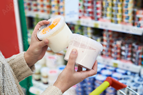 Buyer hands with plastic yogurt jars at grocery