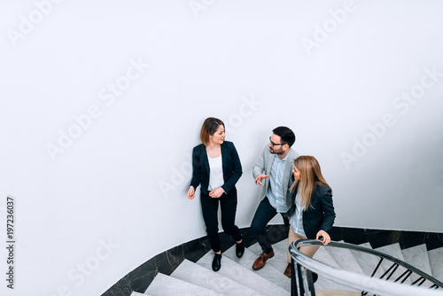 Three people talking while walking up the stairs in the office building.