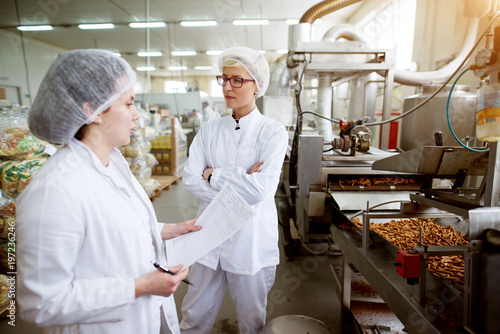 Focused dedicated tired female employee giving rapport in food production factory to her worried and annoyed superior while holding statistic notes and wearing sterile cloths.
