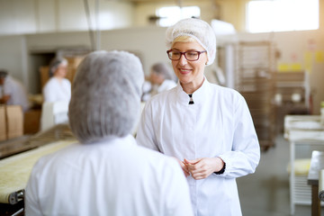 Young cheerful female workers are pleased with the production of food factory line while wearing sterile cloths.