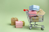 Colorful gifts box, supermarket shopping cart on green background