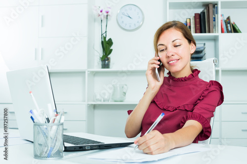 attentive female employee answering on phone and taking notes