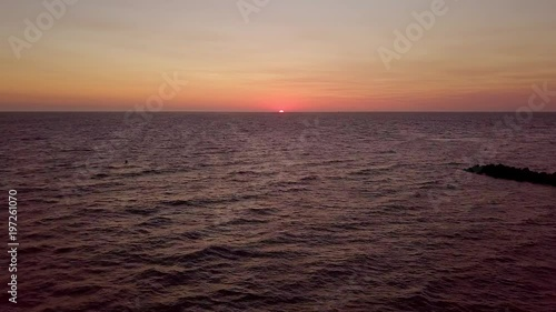 Aerial view of ocean water with slight ripple on background of colorful sky with sun rising above waves.