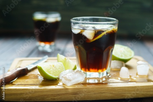 Rum and cola refreshing Cuba Libre alcohol cocktail with lime and ice cubes served on wooden board