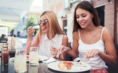 Keuken foto achterwand Pizzeria Pizza time. Young girls eating pizza in a cafe. Consumerism, lifestyle