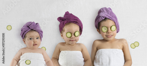 Leinwanddruck Bild Funny baby girl and kids in white towels and terry cloth bath turbans with cucumber face treatments