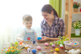 Charming mother and son celebrating Easter. Family celebrating Easter. Parent and kid play indoors. Decorated home and spring flowers - 197309412