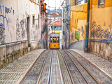 The famous yellow tram rides through the narrow streets of Lisbon in Portugal