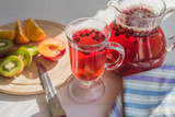 Compote of red berries in a pitcher and a glass, fresh fruit on a rustic table