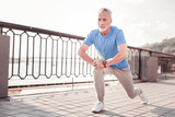 Sport forever. Senior confident unshaken making man exercises on the quay stretching legs and looking aside.