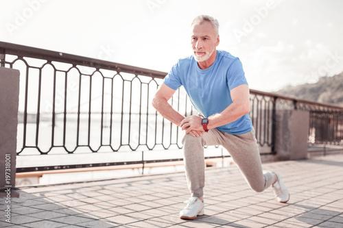 Sport na zawsze. Starszy ufny unshaken robi mężczyzna ćwiczy na quay rozciągania nogach i patrzeje na boku.