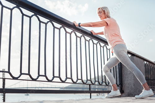 Exercise and training. Thoughtful athletic confident woman standing on the quay warming up relying on the railing.