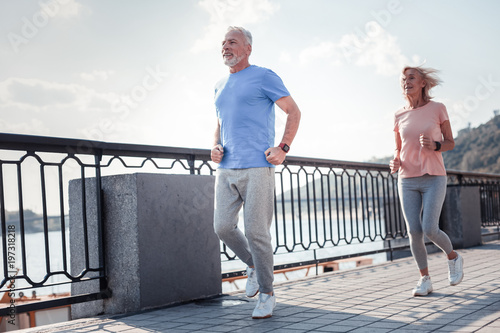 Healthy is the most important. Joyful aged confident man running across the quay with a woman spending time on fresh air and doing cardio exercises.
