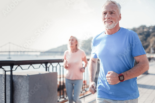 Leinwanddruck Bild Life is good. Satisfied athletic unshaken man spending time on fresh air looking straight and having cardio exercises on the quay.