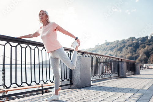 Forever young. Senior athletic pleasant woman standing on the quay holding by the railing and doing exercises.