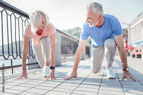 Friendly competition. Joyful senior pleasant couple touching to the ground smiling and preparing to run across the quay.