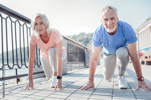 Who will win. Confident friendly aged couple preparing to run across the quay looking straight and touching to the ground.