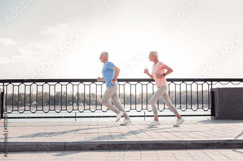 Dont lag behind. Senior sporting persistent couple having common training spending time on fresh air and running across the quay.