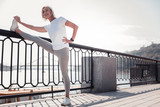 Try to repeat. Sporting cute gray haired woman standing on the quay smiling and stretching her leg.