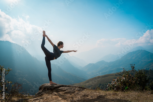 Fototapeta Woman training yoga, mountains on background