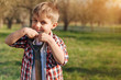 Like gardening. Cheerful little boy standing in the garden and holding shovel while looking at you