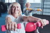 Total joy. Selective focus on a beaming mature lady looking into the camera while exercising with dumbbells on a fitness ball at a gym.