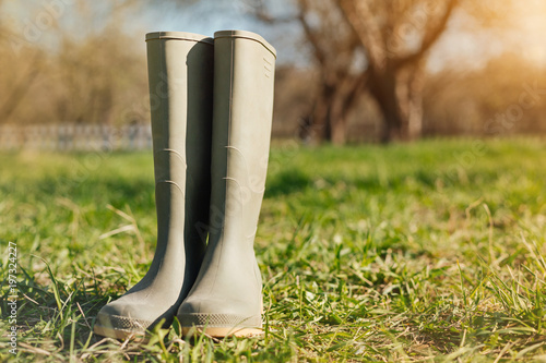 Protective shoes. Close up of a rubber boots standing on the grass in the garden