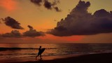 Silhouette of boy running along sea beach at sunset carrying surf board and enjoying beautiful sunset time on coast of Bali island in indonesia. Slow motion video - 197325215