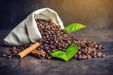 Pile of coffee beans and green leaves in bag on dark background